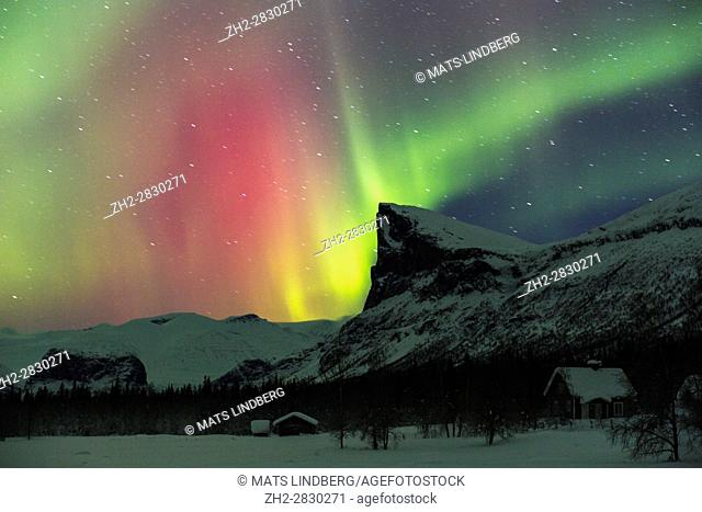 Northern light, Aurora borealis, over Sarek national park taken from Aktse, with an old barn and house, Mount Skerfe and Namatj, slightly movement in the stars