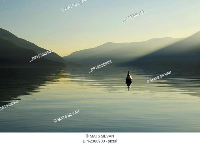 A buoy floats in tranquil lake water with a silhouette of the swiss alps at dawn; Ascona, Ticino, Switzerland