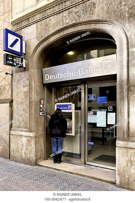 ESP , SPAIN : A customer at a cash machine / ATM of Deutsche Bank in Barcelona , 01.01.2018 - Barcelona, Catalonia, Spain, 01/01/2018