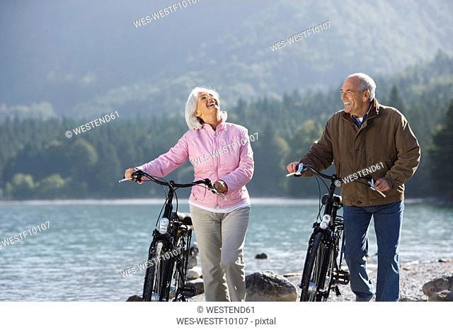 Germany, Bavaria, Walchensee, Senior couple pushing bikes across lakeshore