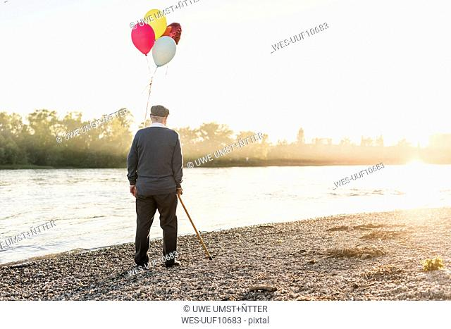 Back view of senior man with balloons standing at riverside in the evening