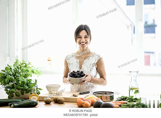 Woman preparing healthy food in her kitchen, holding bowl of cherries