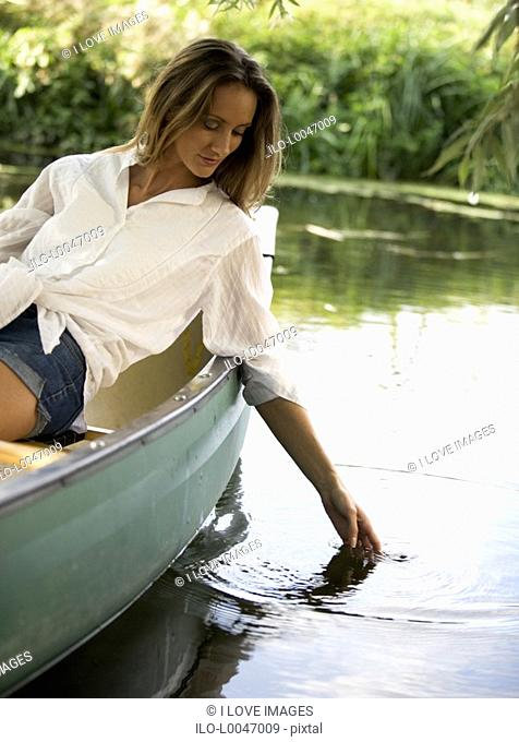 Young woman sitting in a boat, trailing her hand in the water