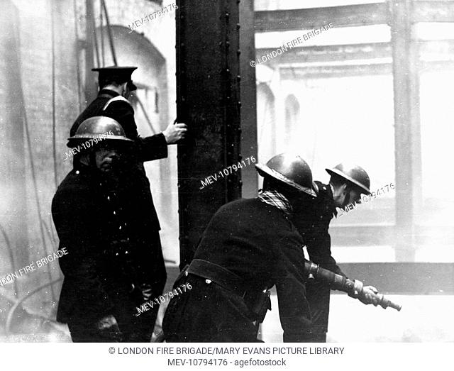Blitz in the City of London -- fire damage due to an incendiary bomb in Bonhill Street, 15 October 1940, with firefighters in action with a hosepipe