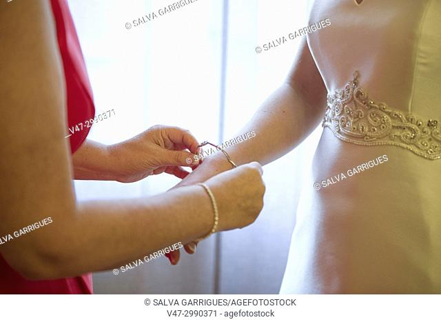 Close-up of the hands of the two sisters at the moment is that she puts the bracelet to the bride on the day of the wedding