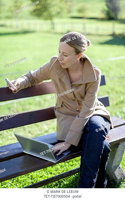Austria, Salzburger Land, Maria Alm, Mature woman sitting on bench and using smart phone and laptop