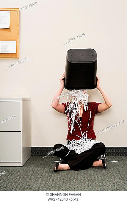Woman tipping shredded paper over herself