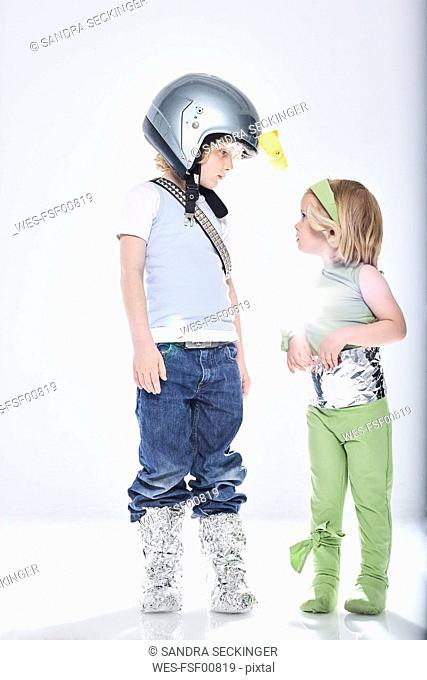 Boy dressed up as spaceman getting in contact with girl dressed up as alien