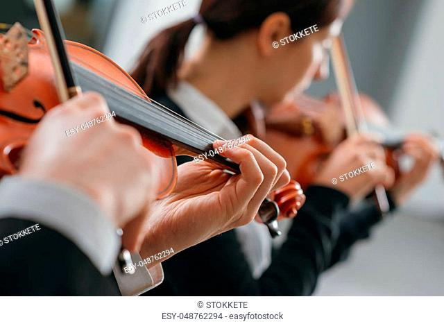 Two violinists performing together hands close up, classical music concert