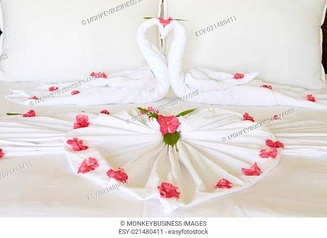 Hotel Bedroom With Flowers Arranged On Sheets