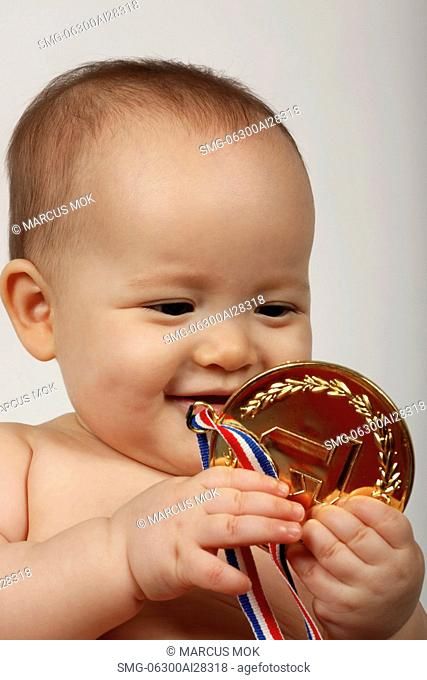 Baby holding gold medal