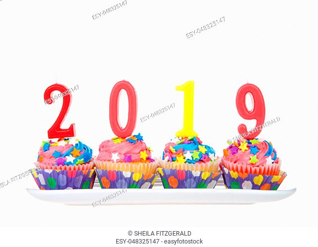 White cupcakes with rainbow colored frosting and brightly colored star candies on a rectangular plate with 2019 candles isolated on white background