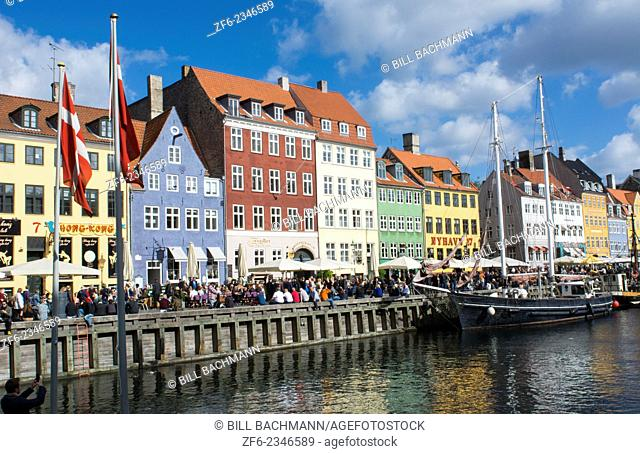 Copenhagen Denmark famous Nyhavn color homes and boats with crowds Kobenhavn tourists