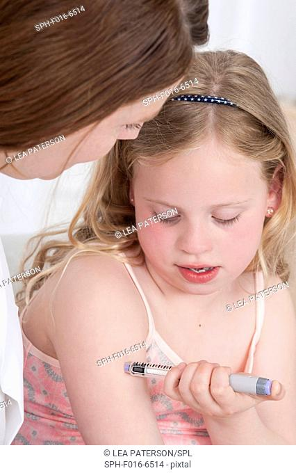 MODEL RELEASED. Girl injecting herself in arm with woman watching