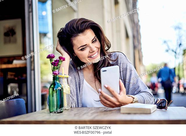 Happy woman looking at cell phone at outdoors cafe
