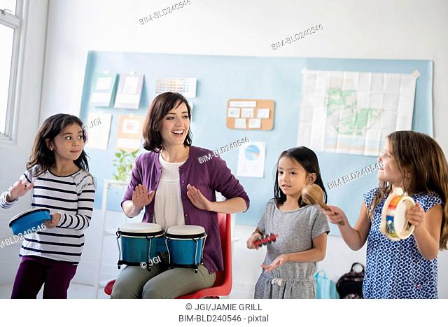 Teacher and girls playing bongos and tambourines in classroom