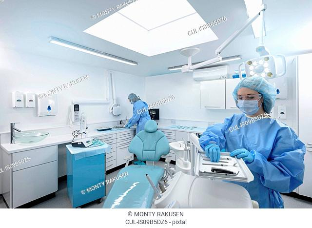 Dentist and assistant preparing in treatment room of dental surgery