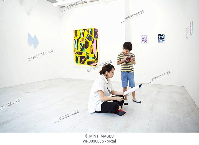 Woman with black hair wearing white shirt sitting on floor in art gallery with pen and paper, boy standing beside her