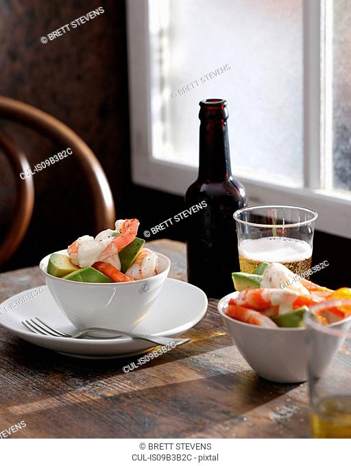 Prawn cocktail and glass of beer on table
