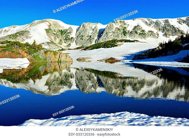 Snowy Range Mountains and alpine lake with reflection in Medicine Bow, Wyoming in summer