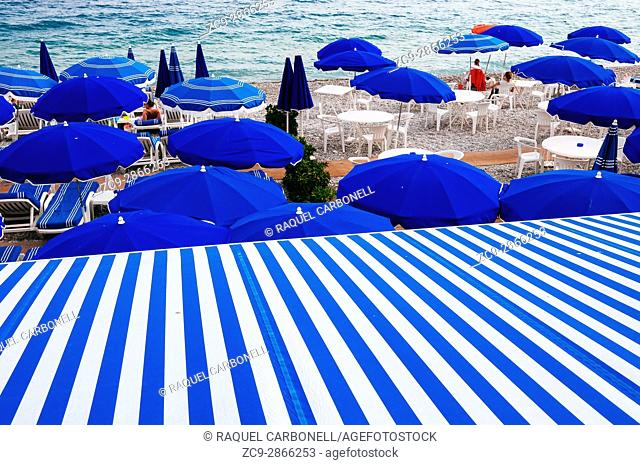 Beach loungers and parasols in 'Neptune Plage' stone beach. Nice, French Riviera, France
