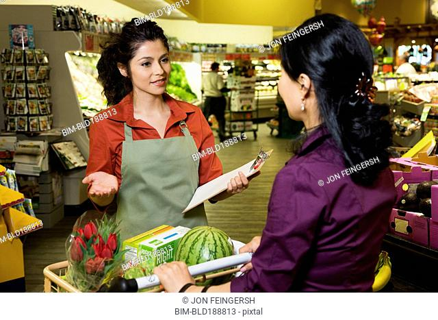 Hispanic clerk helping shopper in grocery store