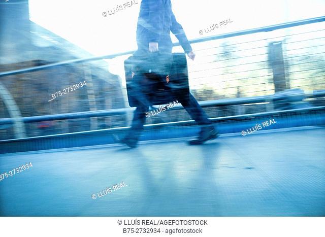 An unrecognizable businessman with portfolio walking down the Millenium Bridge. London, England