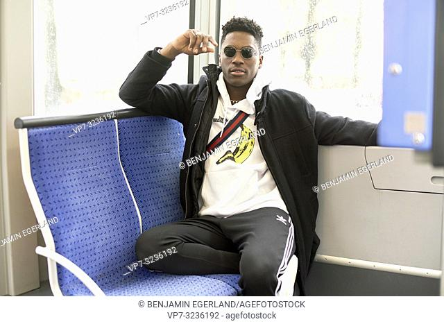 young man sitting in tram, public transport, in Munich, Germany