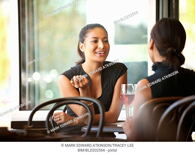 Asian friends sitting together in cafe