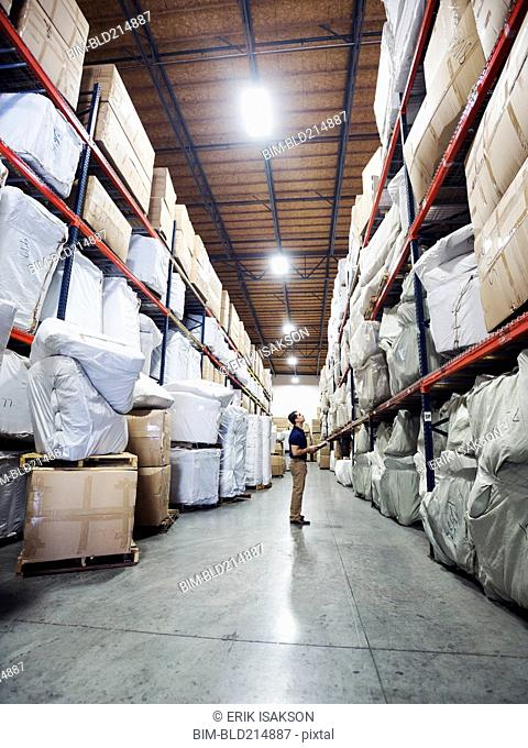 Caucasian worker checking inventory in warehouse