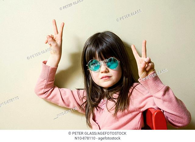 Young girl wearing green colored sunglasses