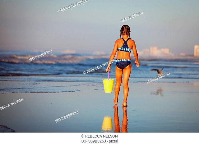 Rear view of girl on beach holding bucket, North Myrtle Beach, South Carolina, United States, North America