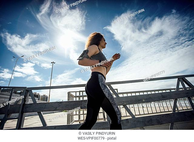 Young athletic woman running on a pier