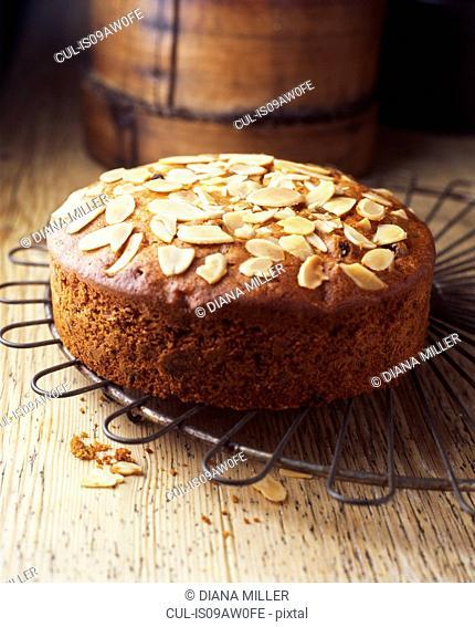 Freshly baked almond fruit cake on vintage cooling rack