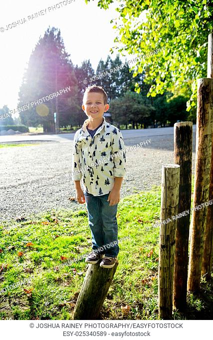 Child standing on a wooden post at an outdoor county park along the McKenzie River in Oregon