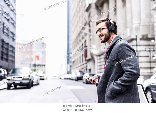 USA, New York City, smiling businessman with cell phone and headphones on the go