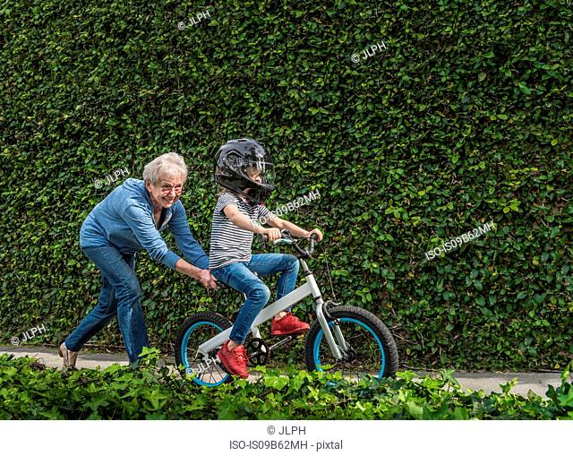 Grandmother pushing grandson on his bicycle