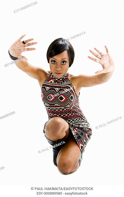 Beautiful African woman in the seventies style sitting on floor and hands towards front, isolated