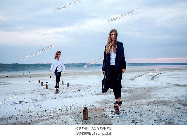 Women balancing on wooden stumps on beach, Odessa, Ukraine