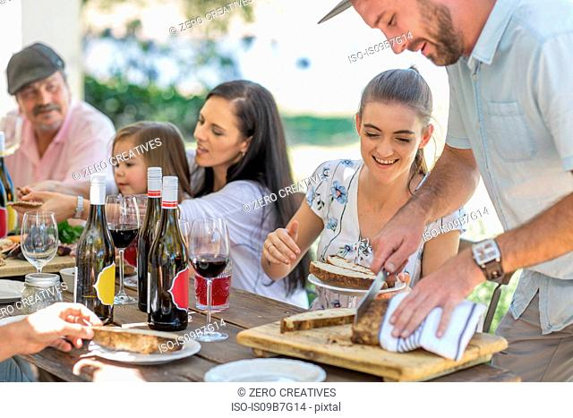 Man slicing bread at outdoor family lunch