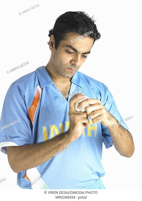 Indian bowler looking at style of holding ball in finger in cricket match MR702A