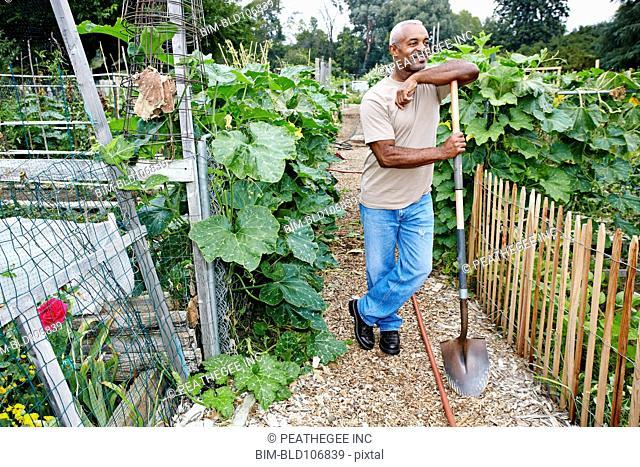 Black man leaning on shovel in community garden