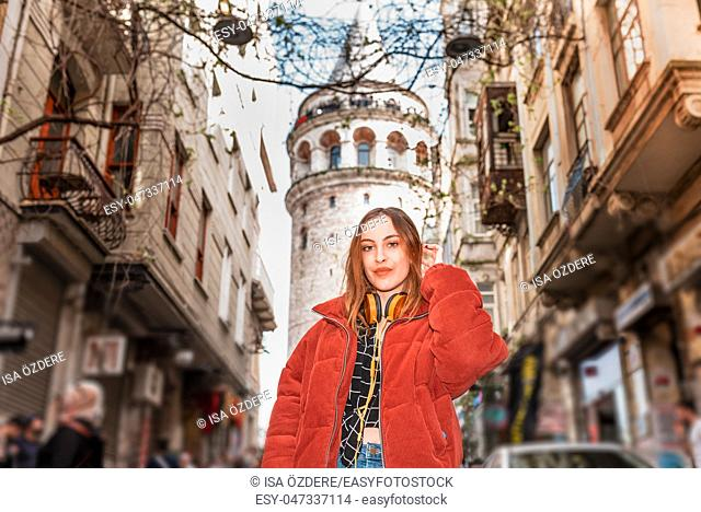 Beautiful attractive happy young trendy girl poses with view of Galata tower in Beyoglu,Istanbul,Turkey