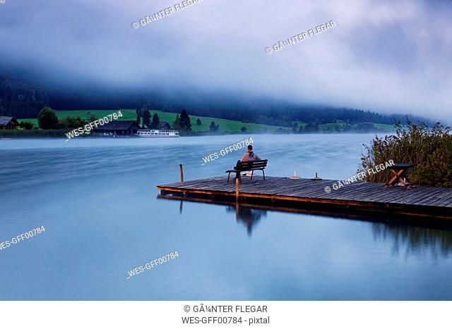 Austria, Carinthia, Man sitting on jetty at Lake Weissensee