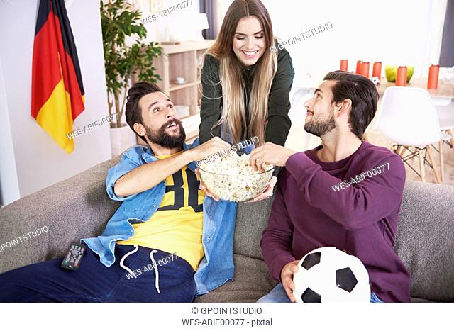 Woman serving snack to friends during football match