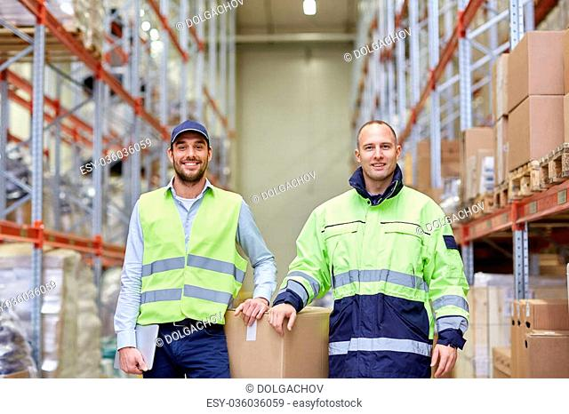 logistic, delivery, shipment, people and export concept - happy men or manual workers with boxes at warehouse