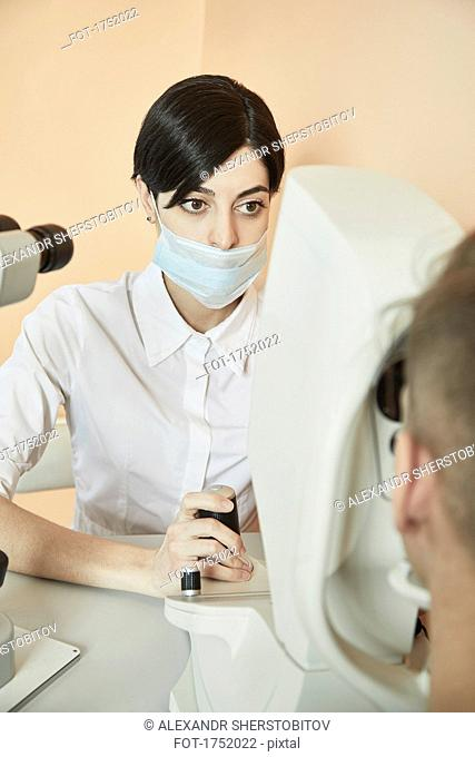 Optometrist examining patient's eye at hospital