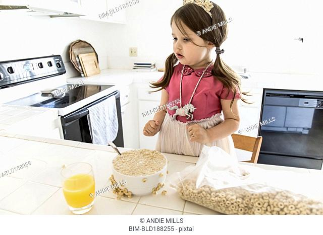 Caucasian girl eating cereal in kitchen