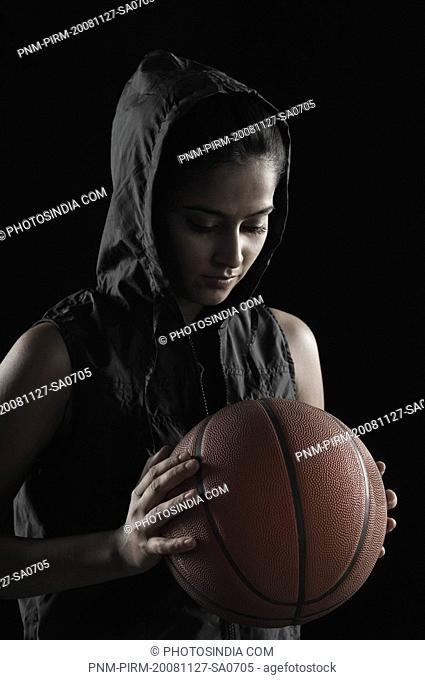 Close-up of a young woman holding a basketball
