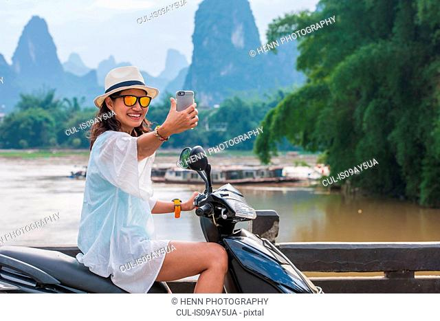 Woman taking a selfie on a scooter with the karst mountain of Guangxi , China